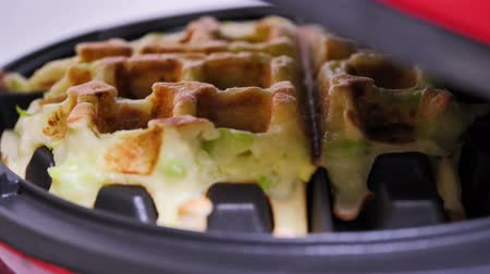 gofret : Raising the lid of an electric waffle iron while preparing zucchini vegetarian waffles. Close up. Healthy eating. Oil free. Stok Video