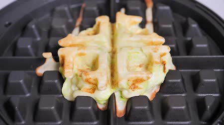 opłatek : Fresh zucchini waffles in an electric waffle iron, with steam. Close-up