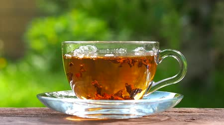 Glass cup with hot tea on a wooden table, against the background of the garden. Stirring tea with a teaspoon. Stock Footage