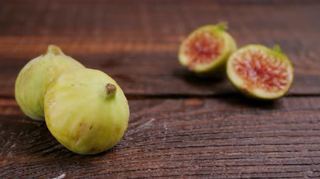 Ripe green and yellow figs on a wooden background. Close Change the focus of the camera. Food concept