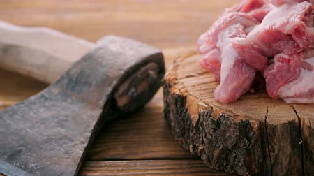 An ax and pieces of chopped meat lie on a wooden table on a wooden board. The passage of the video camera along the table