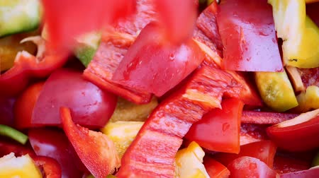 Chopped multi-colored Bell Pepper falls slowly. Slow motion Stock Footage