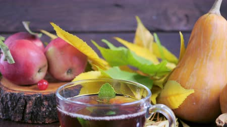 Hot tea on a wooden table against the background of the harvest (pumpkins, apples) and colorful autumn leaves.