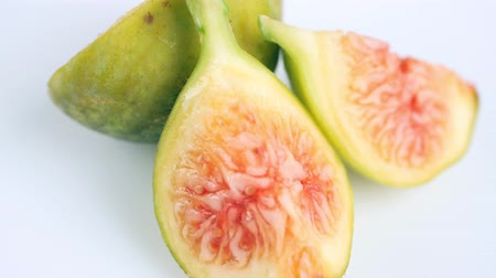 Juicy, ripe, green-yellow figs, whole and slices, on a white background. Close Food concept. Slow rotation.