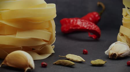 4K video. Pasta: fettuccine nests on a gray background with spices: hot pepper, fennel seeds and chilli peppers. Camera movement from left to right. Close-up. Element for video project. Stock Footage