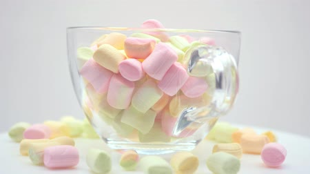 Small multi-colored marshmallows close-up in a transparent, glass mug on a white background. Close Rotation in a circle