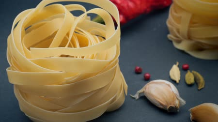 4K video. Pasta: fettuccine nests on a gray background with spices: hot pepper, fennel seeds and chilli peppers. Dimming and lightening. B-Roll, element for video project.