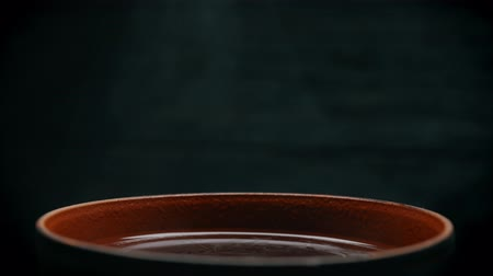 Clay cup with liquid on a dark background. The steam coming out of a mug. Drops Motion steam from the mug is close-up.