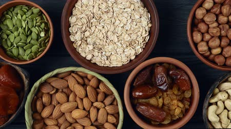 Healthy breakfast. Granola. Oatmeal, barley flakes. Nuts: hazelnuts, almonds, cashews. Dried fruits: raisins, dates, dried apricots. In clay bowls on a black, wooden background. Slow motion.Top view. 4k video Stock Footage