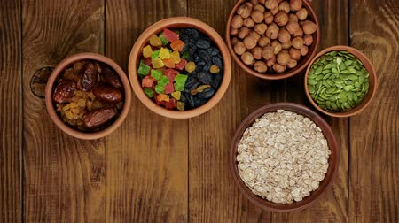 Healthy breakfast. Human hands pick up clay bowls from a wooden table. Granola. Oatmeal, barley flakes. Nuts: hazelnuts, almonds, cashews. Dried fruits: raisins, dates, dried apricots. In clay bowls on a wooden background .Top view. 4k video. Stock Footage