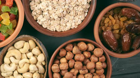 изюм : Healthy breakfast. Granola. Oatmeal, barley flakes. Nuts: hazelnuts, almonds, cashews. Dried fruits: raisins, dates, dried apricots. In clay bowls on a black background. Rotation in a circle. Top view. 4k video. Стоковые видеозаписи