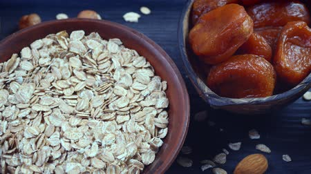 Healthy breakfast. Granola. Oatmeal, barley flakes. Nuts: hazelnuts, almonds, cashews. Dried fruits: raisins, dates, dried apricots. In clay bowls on a black, wooden background. 4k video