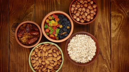 morele : Healthy breakfast. Stop-motion. Granola. Oatmeal, barley flakes. Nuts: hazelnuts, almonds, cashews. Dried fruits: raisins, dates, dried apricots. In clay bowls on a wooden background. Top view. 4k video.
