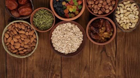 Healthy breakfast. Granola. Oatmeal, barley flakes. Nuts: hazelnuts, almonds, cashews. Dried fruits: raisins, dates, dried apricots. In clay bowls on a wooden background. Top view. 4k video