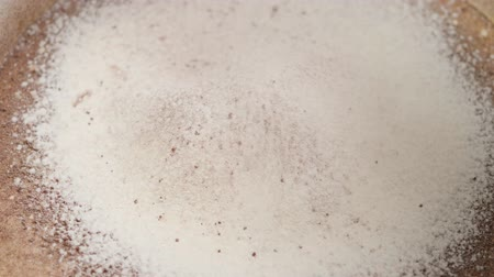 Falling cocoa and flour. Sifting ingredients for the preparation of the dough. Macro Top view. Slow motion. Food concept.