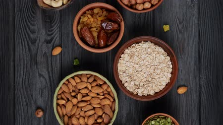 oat flakes : Healthy breakfast. Granola. Oatmeal, barley flakes. Nuts: hazelnuts, almonds, cashews. Dried fruits: raisins, dates, dried apricots. In clay bowls on a black, wooden background. Slow motion.Top view. Stock Footage
