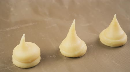 Squeezing dough for eclairs and profiteroles on parchment, from a pastry bag. Close-up. Food concept. 4k video