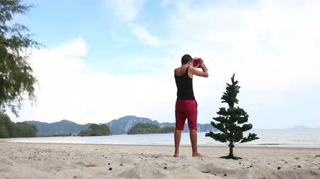 feliz ano novo : guy brings the Christmas tree puts on his hat and carries it away beach with background of the islands