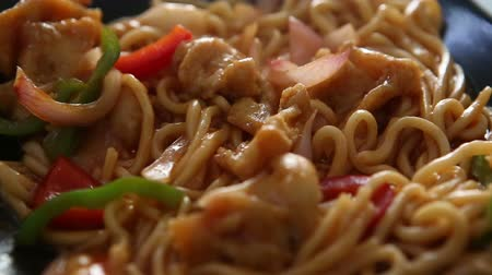 rosół : Chinese dish in a black plate noodles with onions and chicken on the table