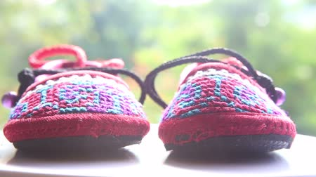 booties : knitted baby shoes with embroidered national with ties on the background greenery