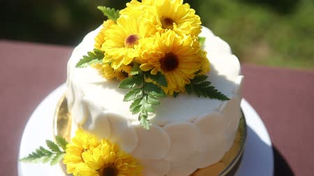 bez : white creamy cake decorated with yellow chrysanthemum flowers on brown table cloth Stok Video