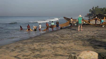 birlik : VARKALA, KERALAINDIA - FABRUARY 12  2012: fishermen pull the network out of the sea near the fishing village   pulled on the shore and tourists taking pictures on Fabruary 12 in Varkala