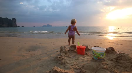 zamek : blonde baby girl in purple swimsuit dance and go to the sea at sunset