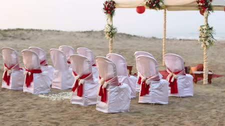cerimônia : the place of conducting Indian wedding ceremony with decorated tent spectators seats rose petals on the ocean sand shore