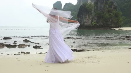 kumlu : young blonde bride turns around barefoot with veil on sandy beach against rocks and sea water background