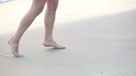 крупный план : girls feet are stepping and splashing through shallow sea water on the beach Стоковые видеозаписи