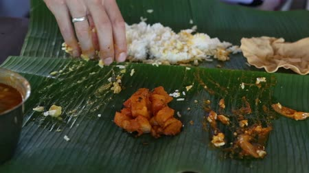 banany : white man eats indian rice with flat cake from banana leaf as the indian people Wideo