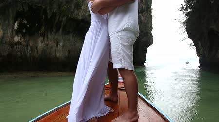 romantic couple : blonde bride and handsome groom stand and kiss on longtail wooden boat in the sea near the cliff lagoon Stock Footage