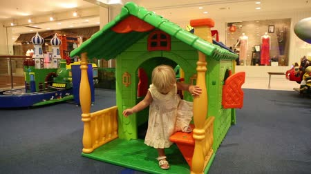 gerekçesiyle : little blonde child plays at toy house in trade mall