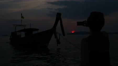 dark bay : asian girl take photograph on telephone of motor longtail boat at deep sunset Stock Footage