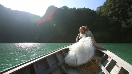 pelyhes : groom embraces and kisses shoulder curly bride in wedding dress sitting in longtail boat against mangrove trees at back light Stock mozgókép