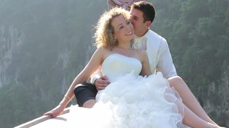 bochecha : strong handsome groom kisses blonde curly bride to cheek sitting in longtail boat against mangrove trees