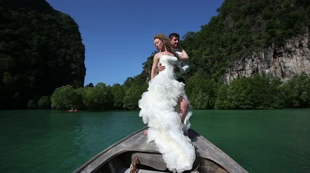 pelyhes : curly blonde bride waves long downy wedding dress poses and clasps to groom standing on longtail boat against mangrove trees Stock mozgókép
