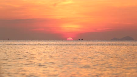 levantar : panorama of boat drifting at background of sun disk rising from behind horizon above sea