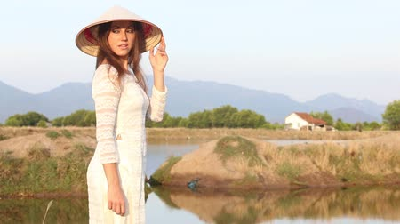 вьетнамский : european blonde girl in vietnamese national costume and hat poses near pond for paddy planting against mountains