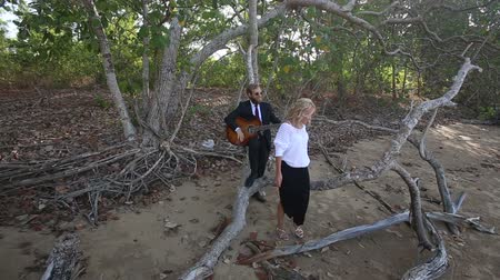 uzun : blonde girl in evening dress stands up of branch and guitarist in black stops to play against tropical trees Stok Video