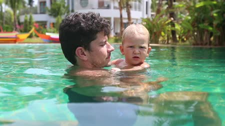 travessura : young father holds in arms blonde little daughter and she plays pranks in swimming pool