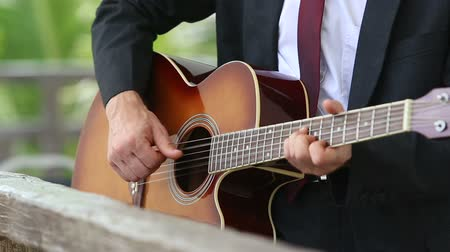 suit and tie : acoustic guitar which blonde bearded man in suit and tie plays