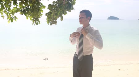 krawat : handsome groom in black trousers sets necktie straight smiling on beach looking at brides wedding dress