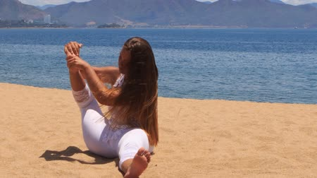 гибкость : blonde girl in white lace costume shows yoga asana foot behind arm on beach against azure sea and hills