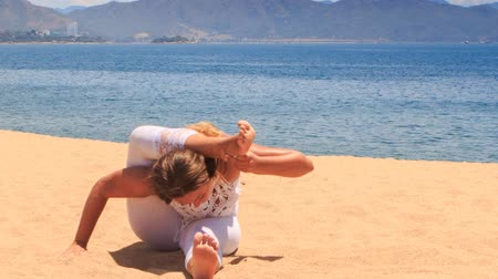 гибкость : blonde girl in white lace costume shows yoga asana forward bend on beach against azure sea and hills Стоковые видеозаписи