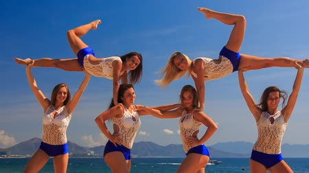 İsveççe : closeup squad of cute cheerleaders in white blue uniform demonstrates stunt Swedish falls and smiles against azure sea
