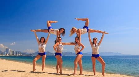 brochura : squad of six cute cheerleaders in white blue uniform demonstrates Swedish falls on beach against azure sea Vídeos