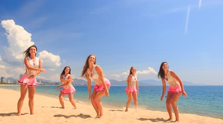 uzun : cheerleaders in white pink uniform dance and show jump stunt on sand beach against sea wind shakes long hair