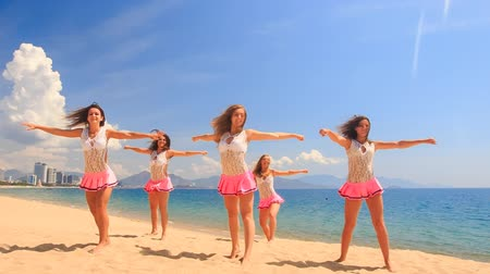 uzun : cheerleaders in white pink uniform dance and show different positions on sand beach against sea wind shakes long hair