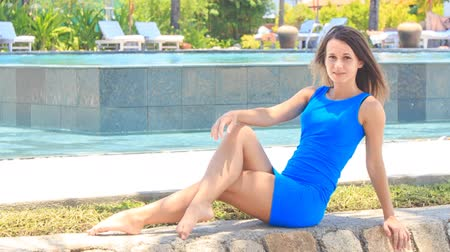 rövid : european slim girl in short blue frock sits on stone barrier bends leg shakes head against pool and palms
